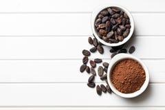 Graines de cacao et poudre de cacao dans des cuvettes Images libres de droits