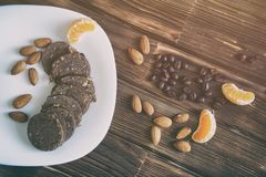 Graines de café, écrous d'amande, tranches de mandarine et pâtisserie de saucisse de chocolat sur une surface en bois Traitement  image stock