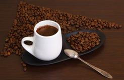 Graines de café avec du café dans la cuvette blanche Photographie stock libre de droits