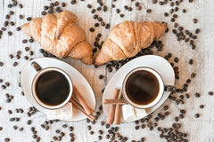 Graines de café avec la tasse de café et le croissant Photographie stock libre de droits