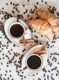 Graines de café avec la tasse de café et le croissant Image libre de droits