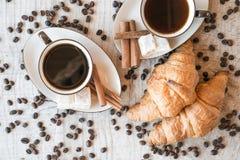Graines de café avec la tasse de café et le croissant Photographie stock