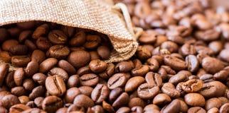 Graines de café, chute hors du sac Le fond des grains de café Panorama_ photographie stock