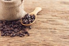 Graines de café dans le sac et la cuillère sur la table en bois supérieure Images stock