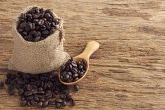 Graines de café dans le sac sur la table en bois supérieure Photographie stock libre de droits