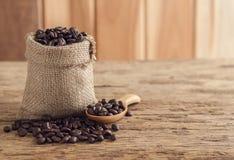 Graines de café dans le sac sur la table en bois supérieure Image stock