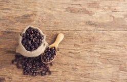 Graines de café dans le sac sur la table en bois supérieure Images stock