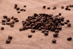 Graines de café de Brown sur la toile de jute Photos stock