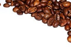 Graines de café frites sur un fond blanc Macro Image stock