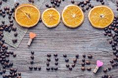 Graines de café sur une surface en bois avec des oranges sèches et un coeur en bois L'amour de mot des grains de café Photographie stock