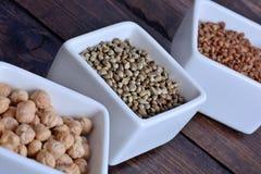 Graines de chanvre avec d'autres graines saines dans cuvettes en céramique images libres de droits
