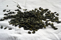 Graines de citrouille épluchées sur une nappe blanche Photo stock