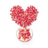 Graines de grenade dans la forme du coeur et la moitié du fruit Photo libre de droits