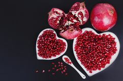 Graines de grenade dans une forme d'un coeur sur le fond en bois Images libres de droits