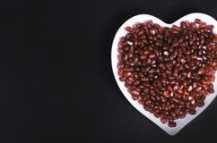 Graines de grenade dans une forme d'un coeur sur le fond en bois Photographie stock