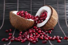 Graines de grenat dans la coquille de noix de coco Photos stock