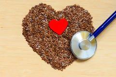 Graines de lin crues en forme de coeur et stéthoscope Photo stock