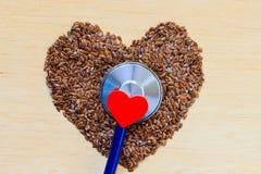 Graines de lin crues en forme de coeur et stéthoscope Photographie stock libre de droits