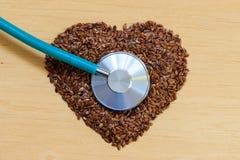 Graines de lin crues en forme de coeur et stéthoscope Photo libre de droits
