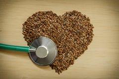 Graines de lin crues en forme de coeur et stéthoscope Photos libres de droits