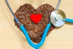 Graines de lin crues en forme de coeur et stéthoscope Photos stock