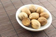 Graines de noix de muscade dans une petite cuvette blanche Photographie stock libre de droits