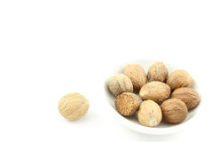 Graines de noix de muscade dans une petite cuvette blanche Image stock