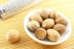 Graines de noix de muscade dans une petite cuvette blanche Images stock