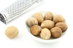 Graines de noix de muscade dans une petite cuvette blanche Photos libres de droits