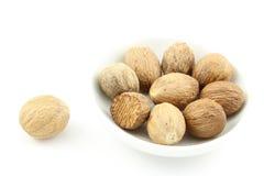 Graines de noix de muscade dans une petite cuvette blanche Image libre de droits