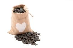 Graines de tournesol noires dans un sac d'isolement photos libres de droits