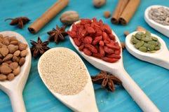 Graines et fruits aromatiques de condiments dans des cuill?res en bois image stock