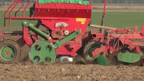 Graines modernes de grain de céréale d'instrument de machine de semeur dans le sol de champ Panorama 4K clips vidéos
