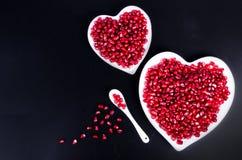 Graines organiques fraîches de grenade dans la cuvette en forme de coeur blanche L'espace libre pour votre texte Photographie stock libre de droits