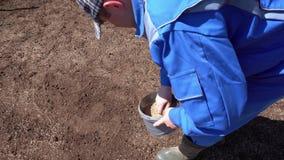 Graines professionnelles de pelouse de truie de travailleur dans le sol Tir de mouvement de mouvement de cardan clips vidéos