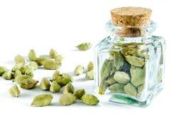 Graines sèches de cardamome dans la bouteille en verre et le tas du cardamome Images stock