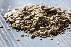 Graines sèches mélangées potiron, sésame, tournesol, lin pour la consommation saine sur la table noire en bois images libres de droits