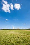 Grainfield and power plant. The picture shows a power plant and a grainfield stock photos