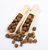 Grains of allspice on white. Grains of allspice on wooden spoon on white background stock photo