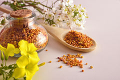 Grains of bee pollen in jar and wooden spoon elevated Stock Photo
