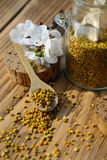 Grains of bee pollen in jar and wooden spoon on wooden table with flowers of spring trees. Apitherapy. Bee products. Royalty Free Stock Images