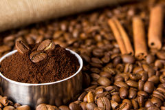 Grains of black coffee, ground coffee and cinnamon. On a background of sacking Stock Image