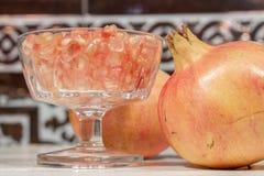 Grains blancs de grenade sur le gobelet en cristal, près des fruits Photos stock