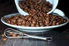 Grains Chocolate with a beater. Chocolate beans spilled from a white cup with beater Royalty Free Stock Images