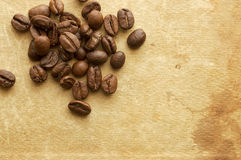 Grains of coffee on background of old book. Royalty Free Stock Photo