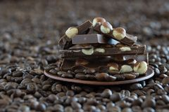 Grains of coffee and chocolate by closeup on a dish. End-view royalty free stock images