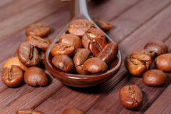 Grains of coffee close-up. Coffee beans are located on a spoon a Royalty Free Stock Images