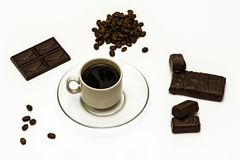 Grains of coffee, a cup of coffee with chocolate sweets and choc. Grains of coffee, a cup of coffee with chocolate and chocolate sweets on a white background Stock Photography