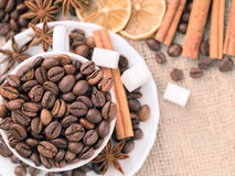 Grains coffee in cup. Cinnamon and anise on a dish. Dried lemon slices and sugar. Stock Photo