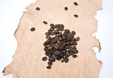 Grains of coffee on a singed paper. Isolated grains of coffee on a singed paper on a white background Stock Photos